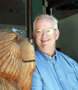 Photo of John Martinelli with a carved bear statue at Lake Tahoe